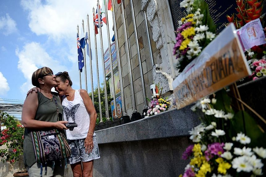Mourners visiting the memorial for victims of the 2002 Bali bombings on the 14th anniversary of the blasts in the tourist district of Kuta near Denpasar, on the Indonesian resort island of Bali, yesterday. The blasts, blamed on the militant Jemaah Is