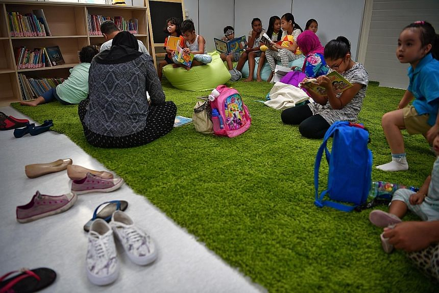Children enjoying the temporary library that opened in Punggol West this month. Among the children-centric plans for the estate are a toy library for toddlers and storytelling sessions run by stay-home mums.