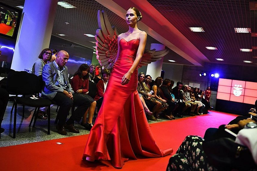 A model wears a creation by designer Micaela Oliveira during a fashion show by Benfica at the Stadium of Light in Lisbon.