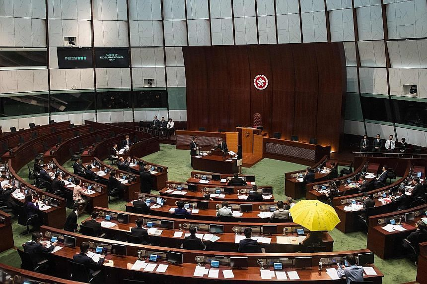 """Ms Yau displaying a flag that reads """"Hong Kong is not China"""", before taking her oath of office yesterday. She is one of the three lawmakers who did not have their oaths approved. Mr Leung Kwok Hung, also known as Long Hair, from the League of Social"""
