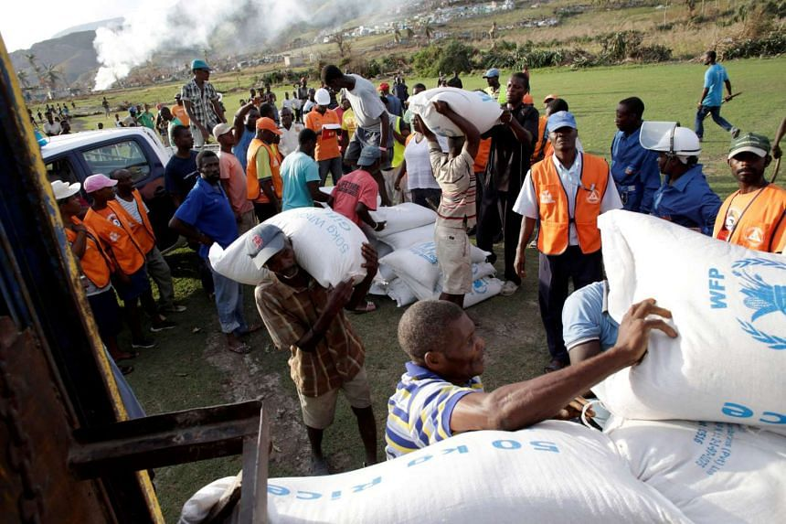 Haitians load supplies delivered by helicopter after Hurricane Matthew in Les Anglais, Haiti, Oct 11, 2016.