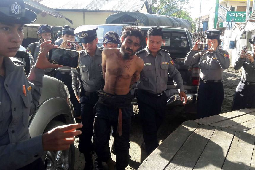 A man suspected of being an attacker during recent border raids is taken to a police station in Sittwe, capital of the Rakhine state on Oct 9, 2016..