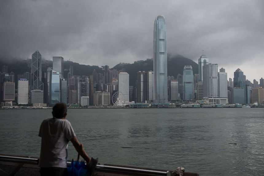 A man looks out towards the Hong Kong skyline, as storm clouds pass on Aug 2, 2016.