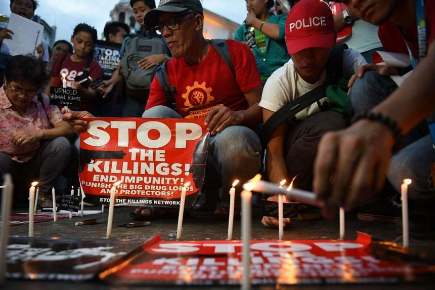 Activists light candles during the candle light vigil for victims of the extra judicial killings in the drug war of the Philippine government in front of a church in Manila.