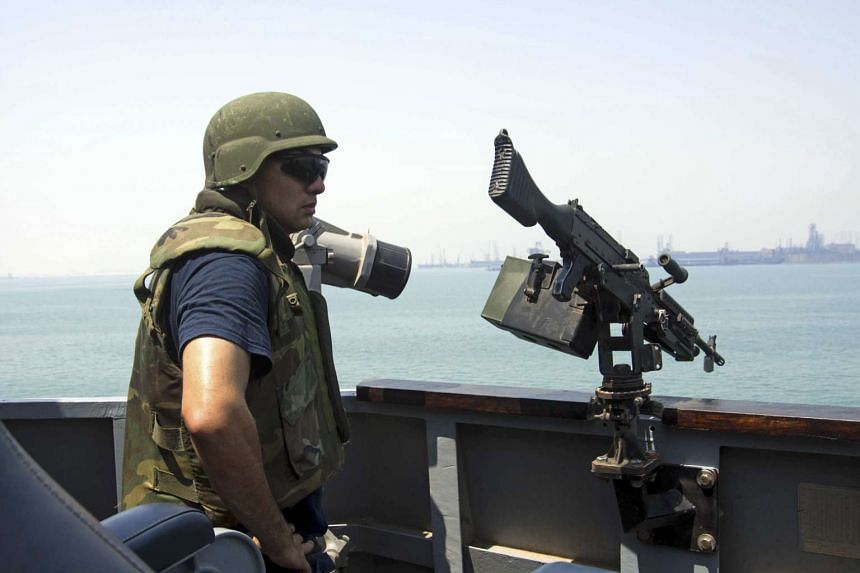 A member of the US Navy scans for threats on the guided-missile destroyer USS Mason in Bahrain Sept 1, 2016.