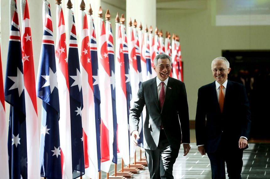 Prime Minister Lee Hsien Loong (left) walks with Australian Prime Minister Malcolm Turnbull (right) at the Parliament House in Canberra during his official visit to Australia.