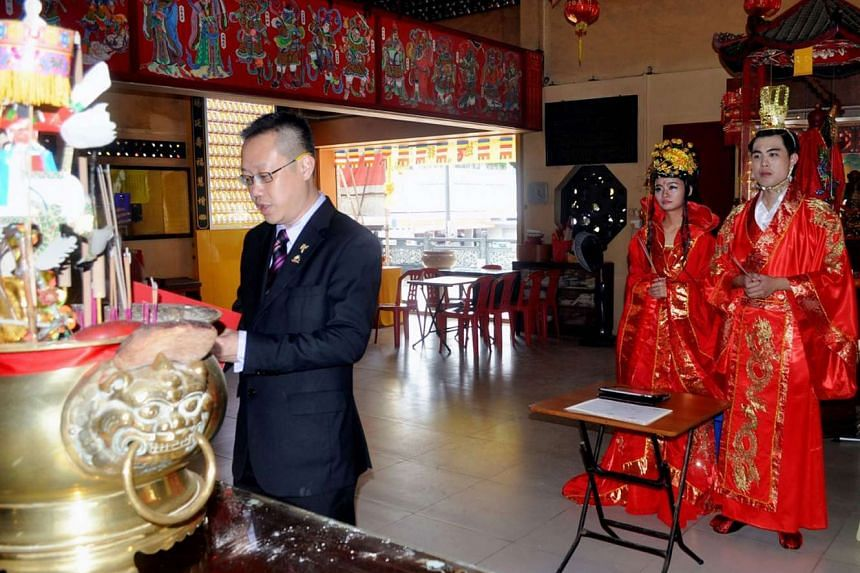 Ms Teo and Mr Lim, clad in traditional costumes bought from e-commerce site Taobao, getting married at Kong Hock Keng Temple in Telok Blangah last June. Master Long was their solemniser.
