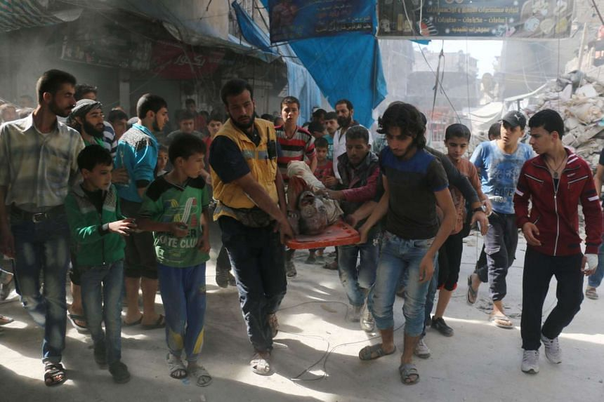 Syrians carry the body of a man following air strikes on the rebel-held Fardous neighbourhood of Aleppo on Oct 12, 2016.