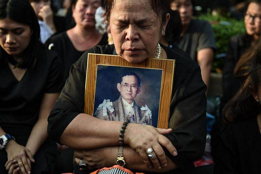 A mourner clutches a picture of Thai King Bhumibol Adulyadej after the hearse carrying the body of the late monarch passes the Grand Palace in Bangkok on Oct 14, 2016.