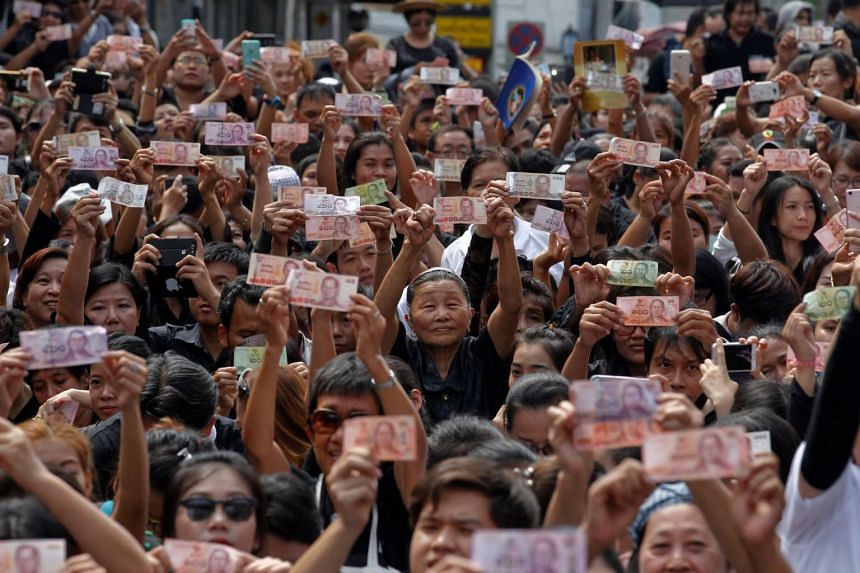 People hold Thai baht notes bearing the portrait of Thailand's King Bhumibol Adulyadej as they wait for the procession carrying his body on Oct 14, 2016.