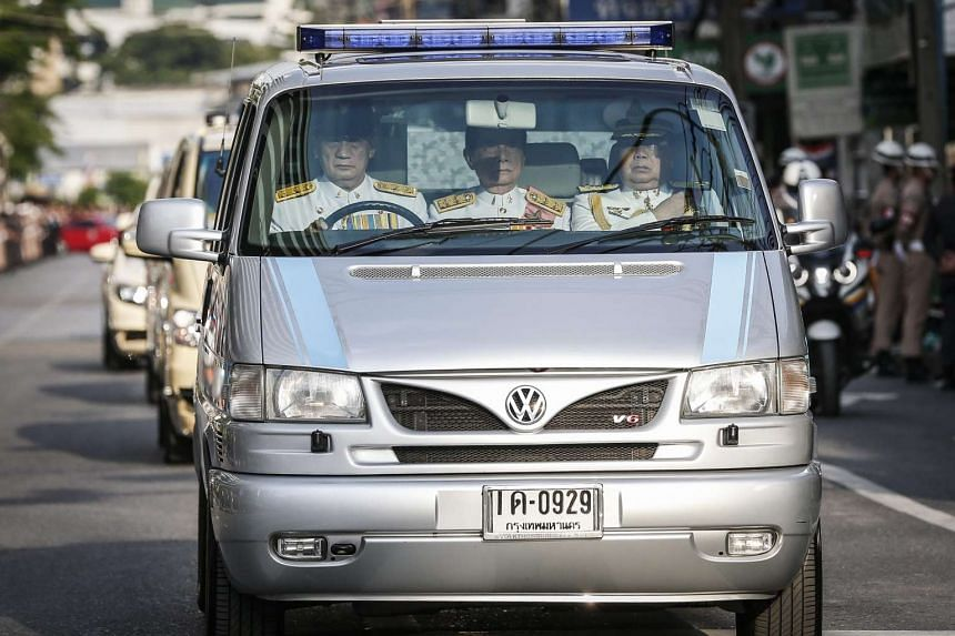 A convoy of vehicles carrying body of late Thai King Bhumibol Adulyadej move toward the Grand Palace as police officers stand guard a long the road in Bangkok on Oct 14, 2016.