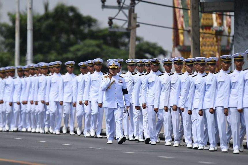 Thai army personel line up a street ahead of a procession for Thailand's King Bhumibol Adulyadej from Siriraj Hospital to the royal palace in Bangkok on Oct 14, 2016.