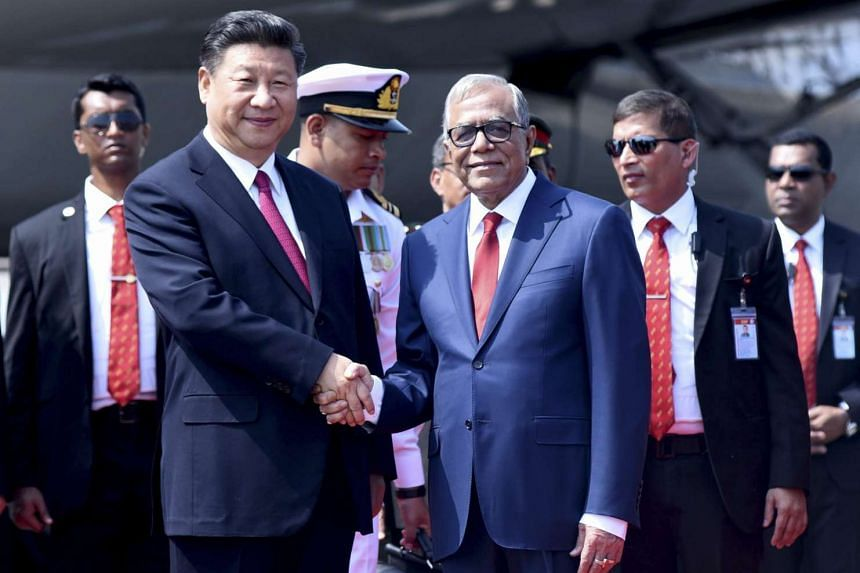 Bangladesh's President Abdul Hamid (right) shakes hand with the Chinese President Xi Jinping after his arrival at the Hazrat Shahjalal International Airport in Dhaka on Oct 14, 2016.