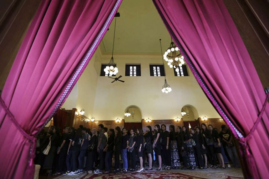 Thai well-wishers stand in a line as they mourn during the royal funeral bathing ceremony for Thai King Bhumibol Adulyadej at the Sahathai Samakom Pavilion inside the Grand Palace in Bangkok on Oct 14, 2016.