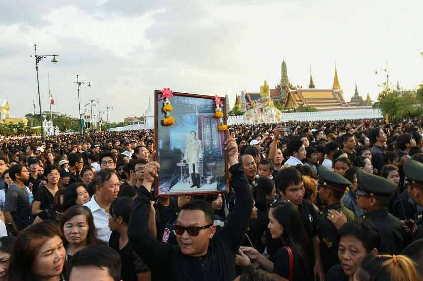 A man holds up a picture of the late King, as thousands line the streets during the procession of Thai King Bhumibol Adulyadej's body to his palace in Bangkok on Oct 14, 2016.