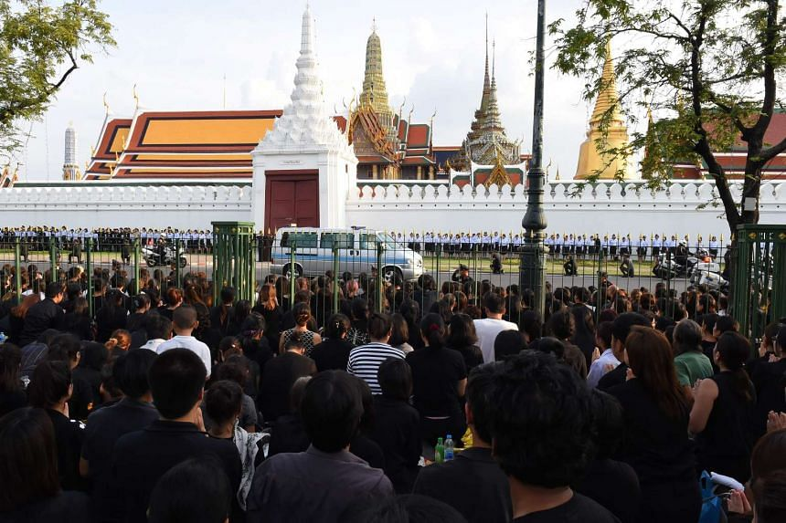 People watch as the van carrying the body of the late King passes by during the procession of Thai King Bhumibol Adulyadej's body to his palace in Bangkok on Oct 14, 2016.