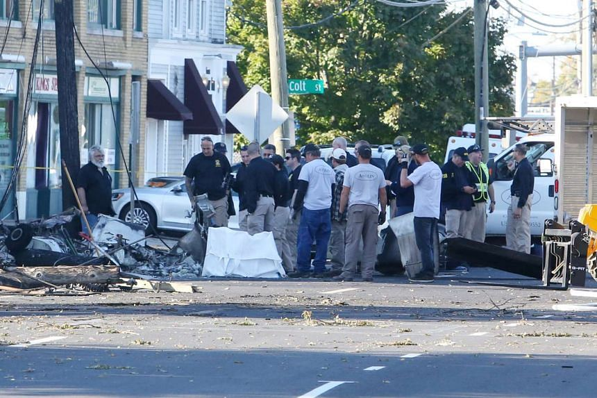 Investigators are seen at the scene of a twin-engine plane that struck a utility pole and burst into flames in downtown East Hartford, Connecticut US, Oct 12, 2016.