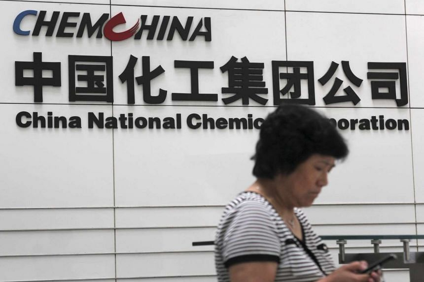A woman checks her phone at the headquarters of China National Chemical Corporation in Beijing.