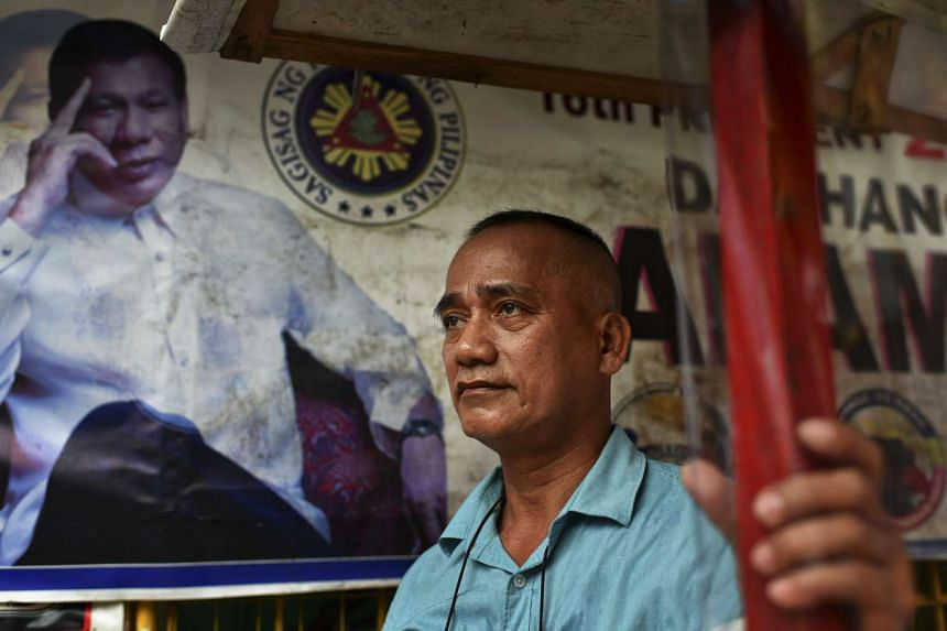 Mr Virgilio Mabag, 54, stands near a poster of President Rodrigo Duterte in Pasay, the Philippines on Oct 10, 2016.