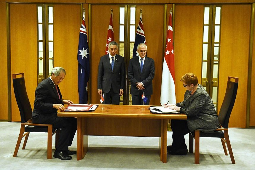 Singapore's Minister for Defence Ng Eng Hen, Prime Minister Lee Hsien Loong, Australia's Prime Minister Malcolm Turnbull and Minister for Defence Marise Payne sign a memorandum of understanding at Parliament House in Canberra, Australia on Oct 13, 20