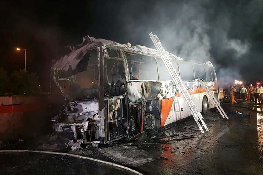 Fire and rescue services attend the scene of a bus accident near Ulsan, on South Korea's south-eastern coast on Oct 14, 2016.