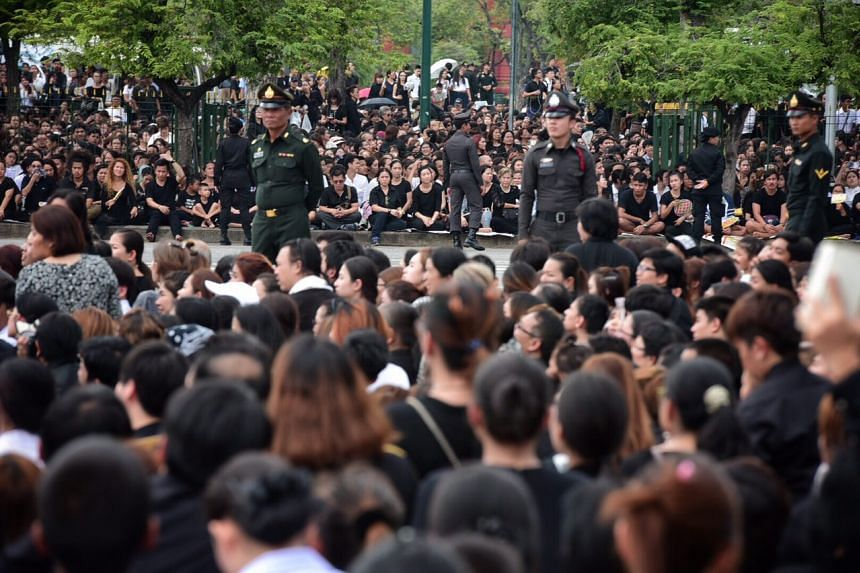 Thais gather along a procession route in Bangkok to pay respect to King Bhumibol Adulyadej, whose body will be brought to the Grand Palace on Oct 14, 2016.
