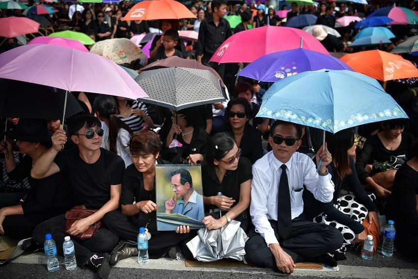 Thais gather outside the Grand Palace to pay respect to King Bhumibol Adulyadej, whose body will be brought in from Siriraj Hospital on Oct 14, 2016.