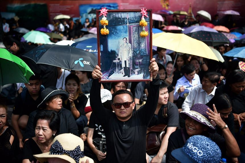 A man holds up a photo of King Bhumibol Adulyadej as he waits outside the Grand Palace for the motorcade transporting the king's body from Siriraj Hospital on Oct 14, 2016.