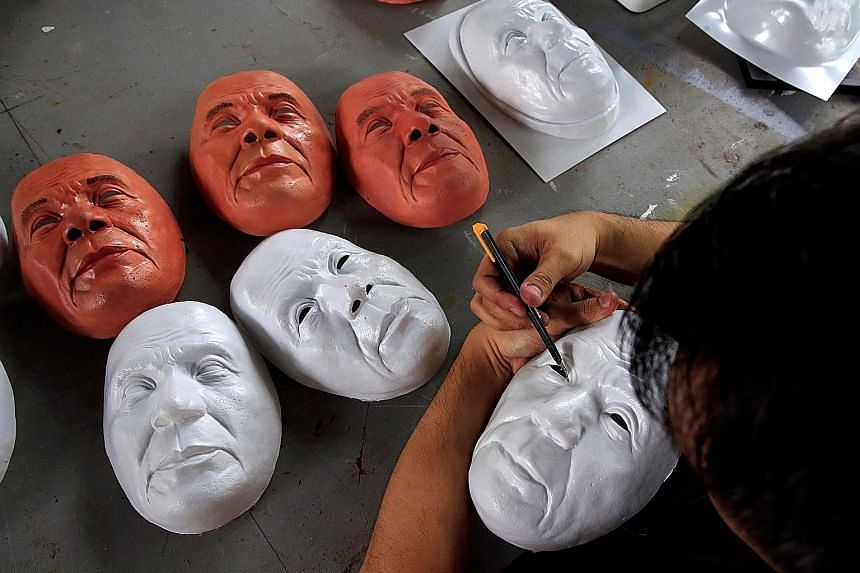 An unfinished Halloween mask depicting Philippine President Rodrigo Duterte being trimmed by industrial engineer and professor John Tan at the College of Fine Arts of the University of the Philippines in Quezon City, Metro Manila, yesterday.