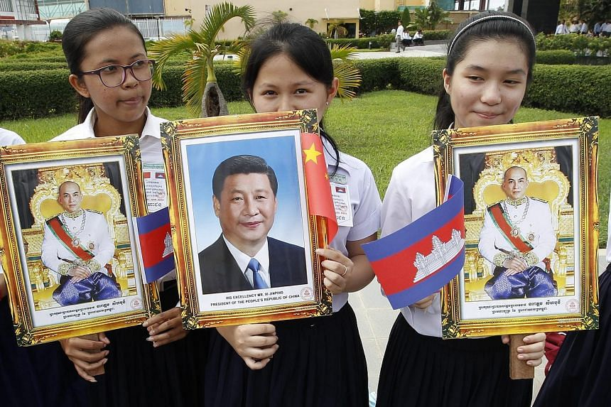 Students with portraits of Cambodian King Norodom Sihamoni and Mr Xi at Phnom Penh's international airport yesterday. At least 28 deals were set to be inked when Mr Xi met Cambodian PM Hun Sen.