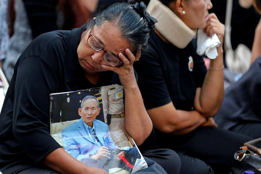 A woman holds a portrait of Thailand's late King Bhumibol Adulyadej at the Siriraj hospital in Bangkok, on Oct 14, 2016.