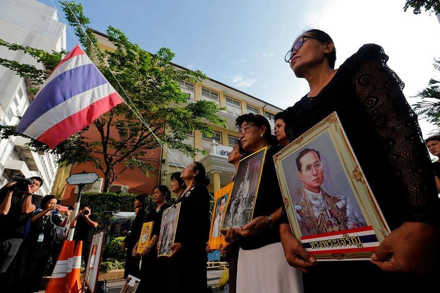 People hold portraits of Thailand's late King Bhumibol Adulyadej as they sing a national anthem at the Siriraj hospital in Bangkok, on Oct 14, 2016.