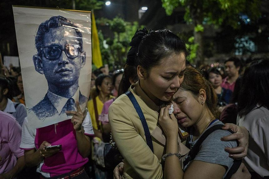 People react moments after the announcement of the death of King Bhumibol Adulyadej outside the hospital where he was being treated in Bangkok.