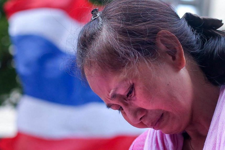 A Thai woman cries prior to the announcement of Thai King Bhumibol Adulyadej's death outside the Siriraj Hospital in Bangkok.