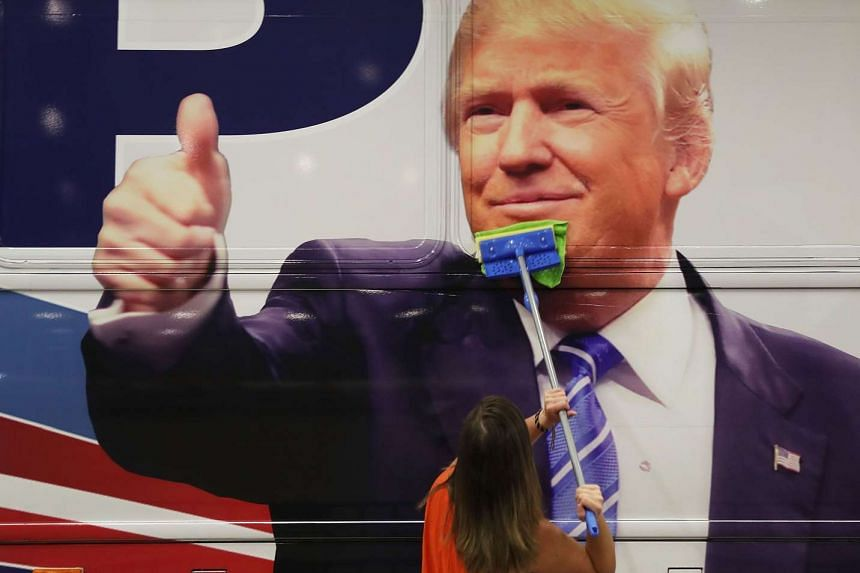 Bailey McDaniel wipes the side of Trump's campaign bus on Oct 13, 2016.