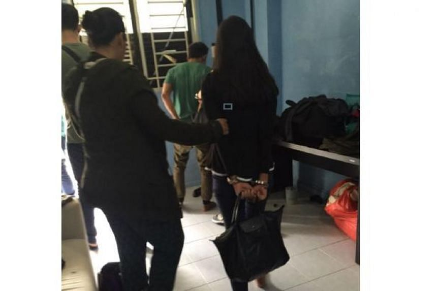 CNB officers escorting arrested drug suspects, during a 11-day island-wide operation from Oct 3 to 14, 2016.