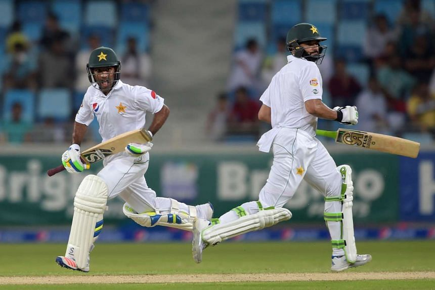 Pakistani batsmen Asad Shafiq (left) and Azhar Ali run between the wickets on the opening day of the first day-night Test between Pakistan and the West Indies at the Dubai International Cricket Stadium in the Gulf Emirate on Oct 13, 2016.