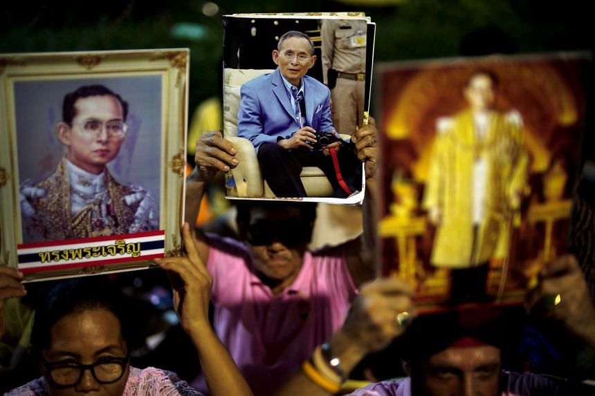 People hold pictures of Thailand's King Bhumibol Adulyadej after hearing news of his death on Oct 13, 2016.