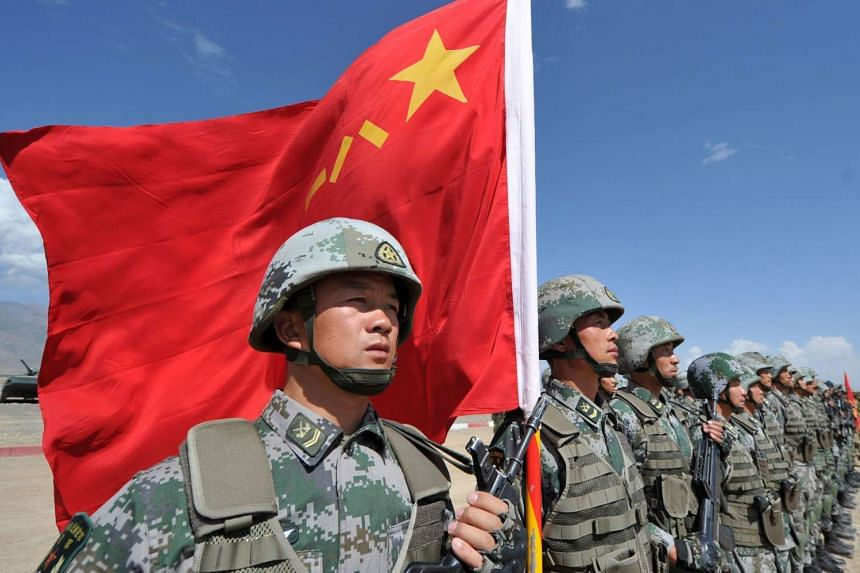 A Chinese soldier holds a Chinese flag during Peace Mission-2016 joint military exercises of the Shanghai Cooperation Organization (SCO) in the Edelweiss training area in Balykchy some 200 km from Bishkek on Sept 19, 2016.