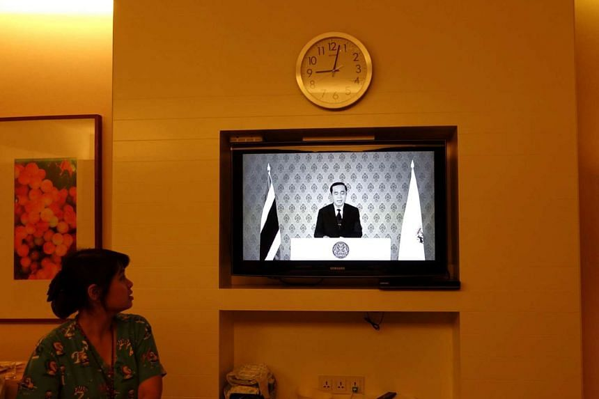 A nurse watches a TV broadcast in black and white of Thai Prime Minister Prayuth Chan-ocha after King Bhumibol Adulyadej's death at a hospital in Bangkok, Oct 13, 2016.