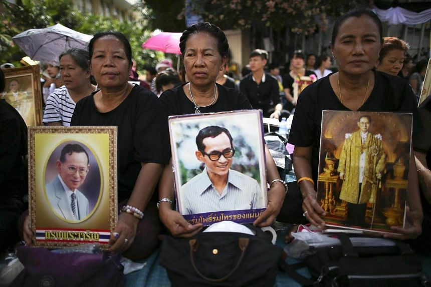 Thai well-wishers wearing black mourn with portraits of late Thai King Bhumibol Adulyadej ahead of a procession to transport the king's body outside Siriraj Hospital in Bangkok on Oct 14, 2016.