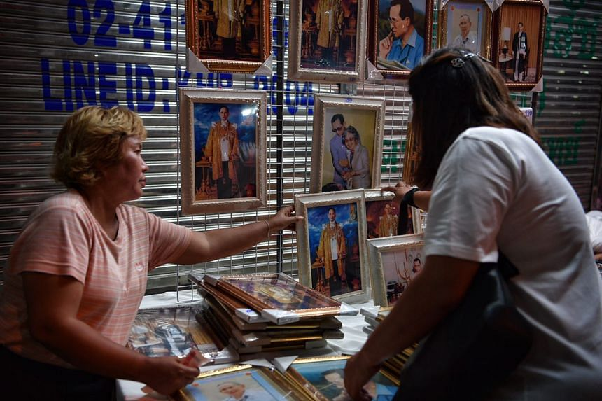 A woman sells pictures of the King outside Siriraj Hospital on Oct 14, 2016.