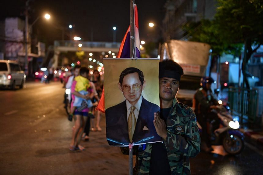 A man holds a picture of the King outside Siriraj Hospital on Oct 14, 2016.