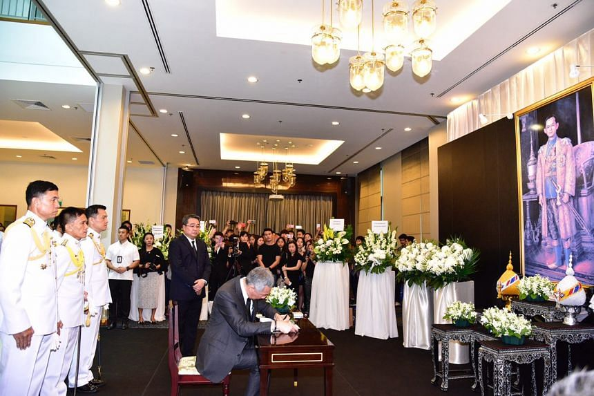 Prime Minister Lee Hsien Loong pens a message in the condolence book for late King Bhumibol Adulyadej at the Thai Embassy in Singapore on Oct 14, 2016.