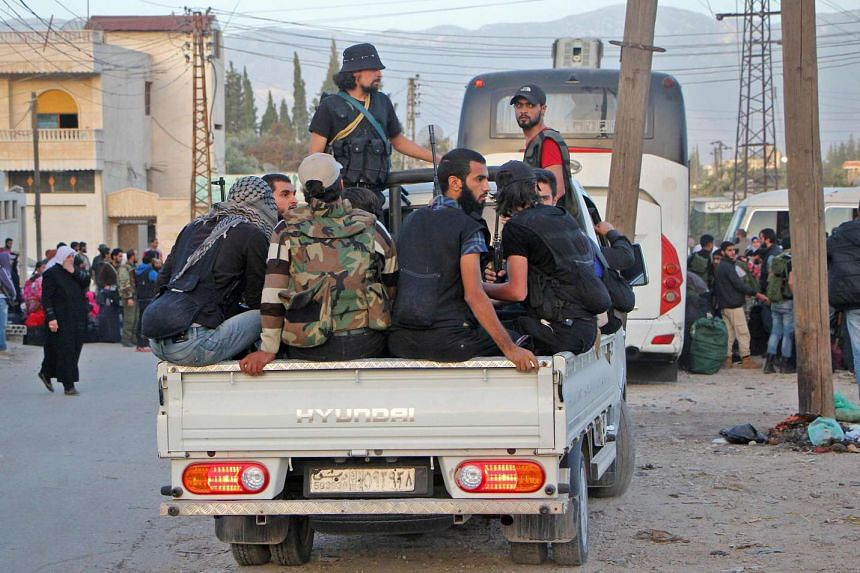 Rebel fighters arrive in Idlib following their evacuation from Qudssaya and al-Hamah, neighbourhoods of the Syrian capital, on Oct 14, 2016.