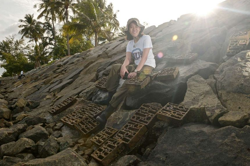 Dr Loke with some of the more than 700 experimental concrete tiles – each measuring about 20cm by 20cm – fixed onto the sea walls surrounding Pulau Hantu. In her latest effort, she is working on how best to arrange the tiles, so that they can be