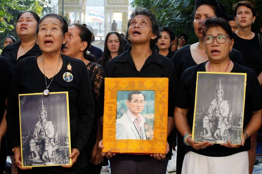 People hold portraits of Thailand's late King Bhumibol Adulyadej as they sing a national anthem at the Siriraj hospital in Bangkok, Thailand, Oct 14, 2016.