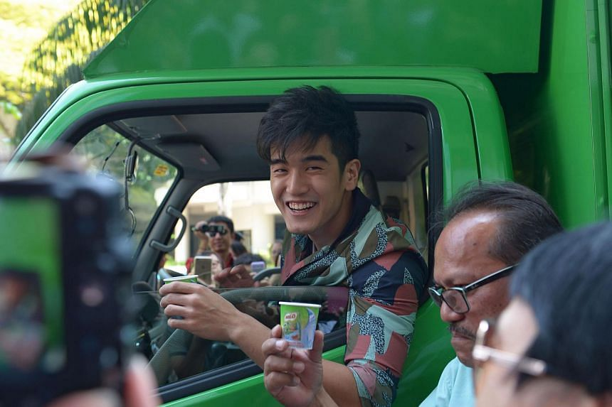Nathan Hartono arrives at Bugis+ in a milo van with driver of milo van, Mr Suderis Ismail (right). Mr. Ismail has been driving a milo van for the past 20 years.
