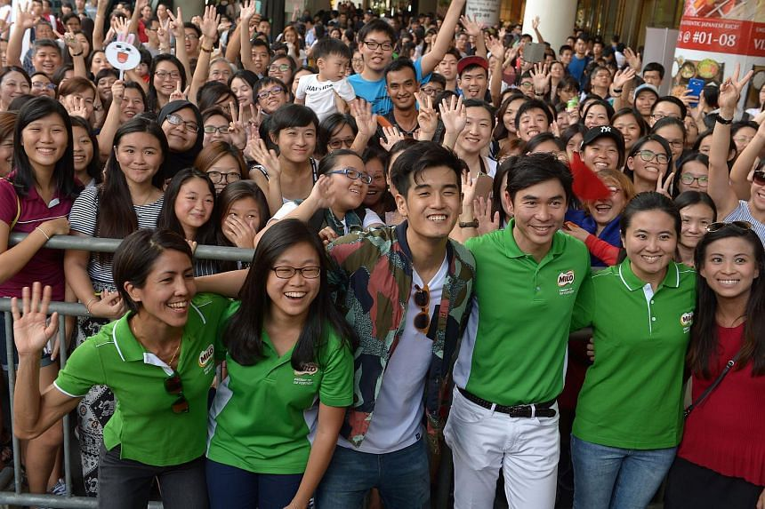 Nathan Hartono posing for a photo with fans at Bugis+ on Oct 15, 2016.