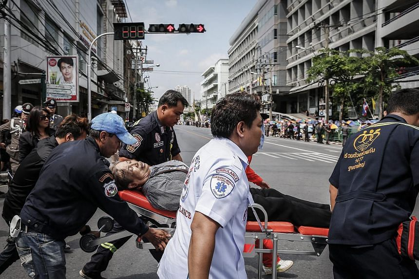 Thai paramedics carry a well-wisher on a stretcher who fainted while waiting for the procession to move the body of the King Bhumibol Adulyadej outside of the Siriraj Hospital in Bangkok on Oct 14, 2016.